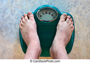 Health - Body Weight - A man weighs himself on a scale.