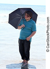 Smiling Teen With Umbrella In Surf