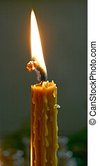 Alone candle flame upon black background
