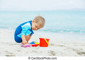Boy playing with beach toys on tropical beach - Cute baby...