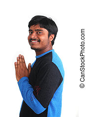 Young guy in praying stance but relaxed and smiling