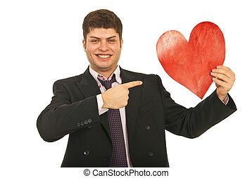Happy business man pointing to heart shape isolated on white...