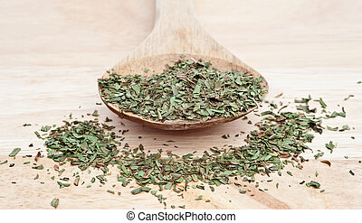 Chopped tarragon on wooden serving spoon with selective...
