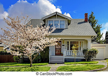 Little old cute house with a blooming cherry tree - Small...