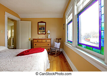 Yellow bedroom with white bed and wood dresser.