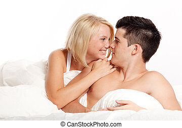 Loving affectionate heterosexual couple on bed.