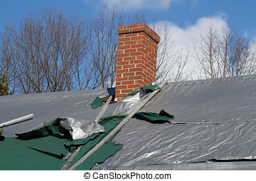 torn Roof Covering - Shingle roof covered with plastic tarps...