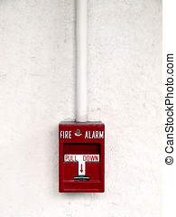 Fire Alarm - Red fire alarm mounted on a textured concret...