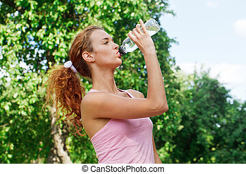 Woman drink water after jogging