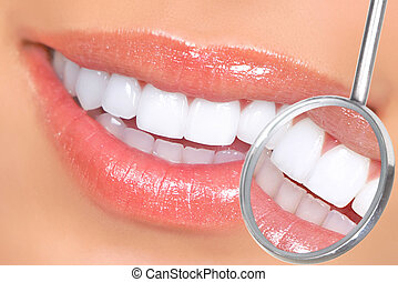 teeth - Healthy woman teeth and a dentist mouth mirror
