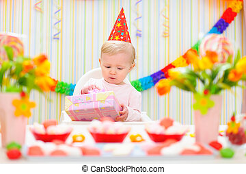 Surprised baby looking on present on first birthday