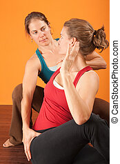 Yoga Coach - Yogasana coach with student stretching over...