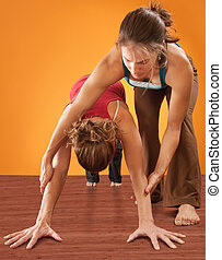 Woman Practicising Yoga - Yoga instructor helping student...