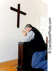 Wooden Cross Prayers - Man praying and kneeling in front of...