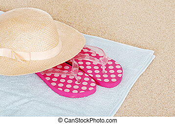 sandals hat on a beach towel - top view of sandals hat on a...