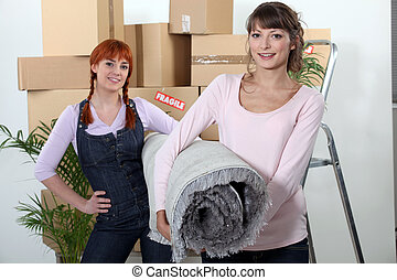 two girlfriends moving in their new apartment