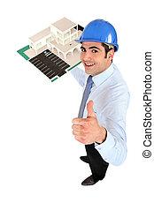 Male architect holding model housing