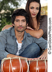 a couple posing near djembe
