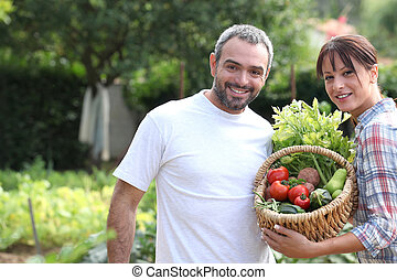 A couple taking care of their vegetable garden