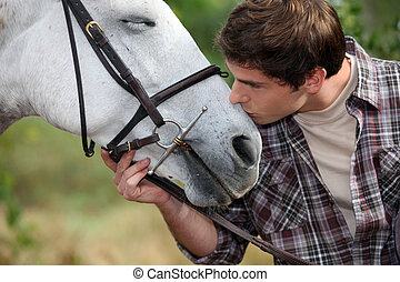 A man patting his horse