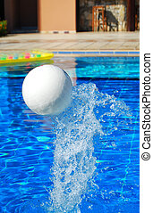 pool fun - A plastic football comes splashing out of a...