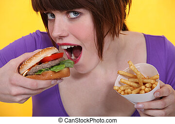 Woman eating a burger and chips