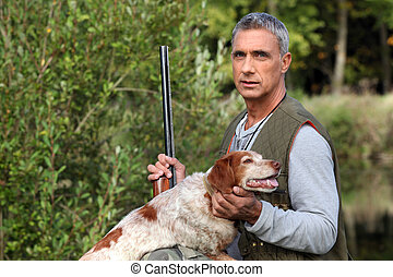 hunter taking a rifle and caressing a hunt dog