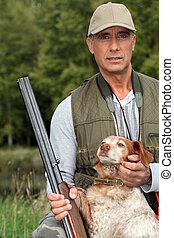 Hunter with a shotgun and dog
