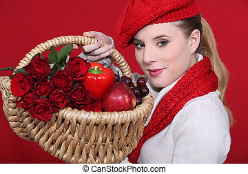 lovely blonde carrying basket filled with red and dressed to...