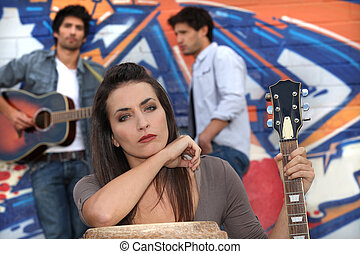 musicians in front of a tagged wall