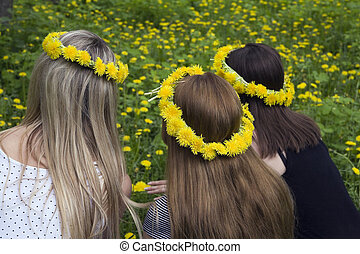 three girls with long hairs in wreaths from dandelions on a background of field with flowers