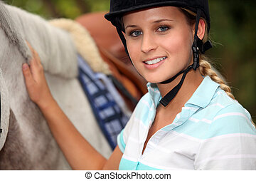 A horseback rider with her horse