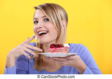 young woman eating a piece of cake
