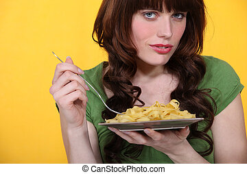 A woman eating pastas.