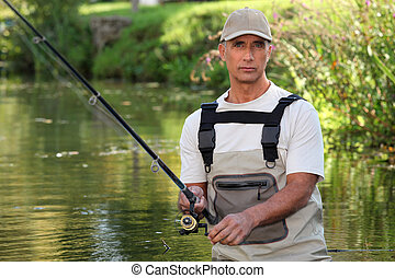 Mature man fishing in a river