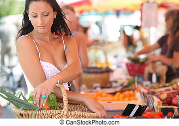 sexy brunette buying vegetables at open air market