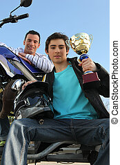 A man with a motorcycle and a trophy