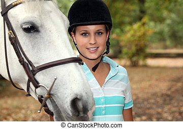 Blond teenager stood with horse