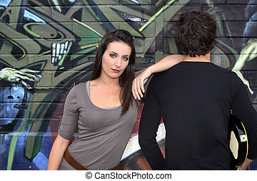 Couple hanging out by a wall painted with graffiti