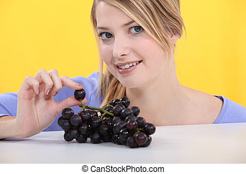 Woman with a bunch of black grapes