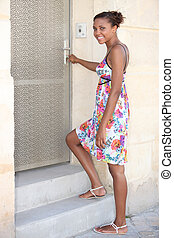 Young woman unlocking her front door
