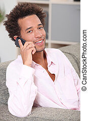 Young man making a call at home