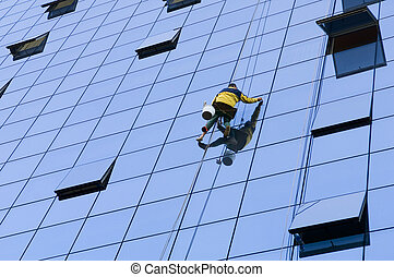 Worker washing windows extremely high