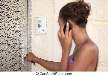 Woman unlocking the door to her apartment building