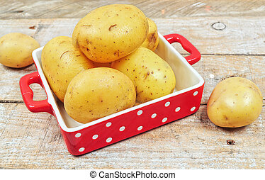 Raw potatoes in red tray