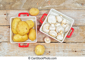 Raw mushrooms and potatoes in red trays