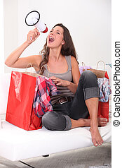 Studio shot of a woman with shopping bags and a loudspeaker