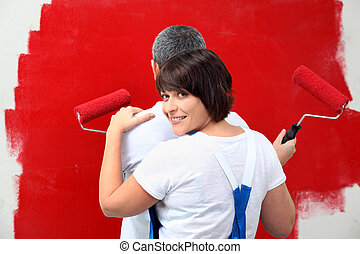 a man and his wife painting a wall