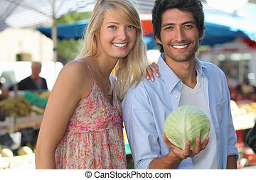 Couple in a market with a cabbage.