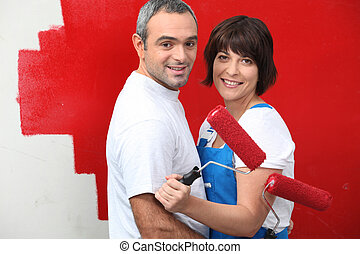 Couple painting a wall red